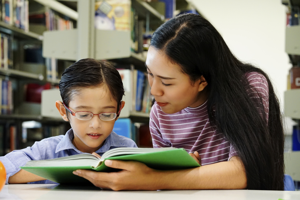 Tutor is helping a kid to read